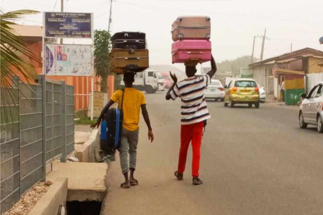 Two men in Ghana are carrying suitcases down the street using their heads